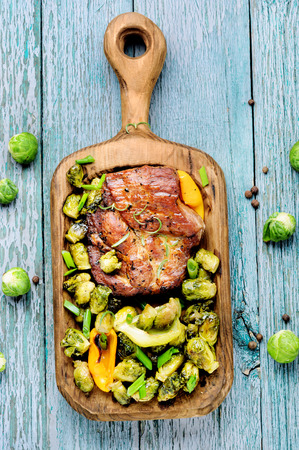 Juicy steak medium rare beef on wooden kitchen board.Grilled meat with Brussels sprouts.BBQ 版權商用圖片