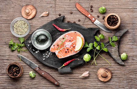 Raw salmon steak on retro cutting board.Fish salmon steak on a fish shaped board