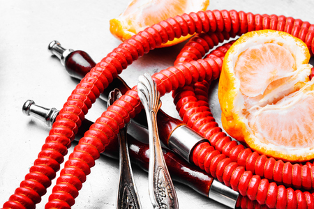 Eastern smoking hookah with mouthpieces with tangerine flavor.Shisha advertising.Mandarin smoke shisha Фото со стока