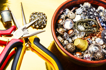 Jewelry and precious stones on gold background.Tools for jewelry making.