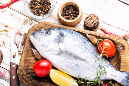 Fresh uncooked dorado or sea bream fish with herbs and spices on cooking board