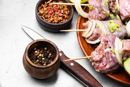 Raw beef kebab in kiwi marinade on a wooden background
