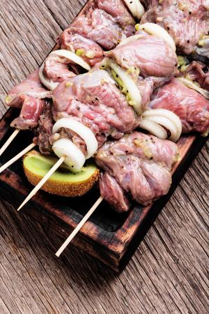 Raw spicy beef shish kebab on a cutting board