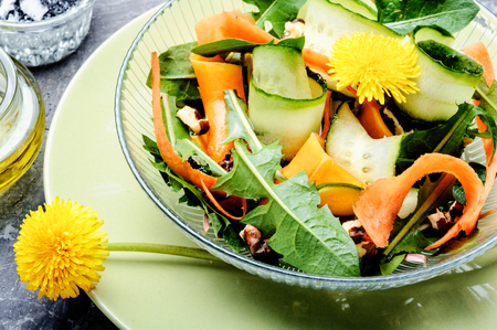 Salad with dandelions flowers,cucumber, arugula and carrot.Fresh vegetable salad