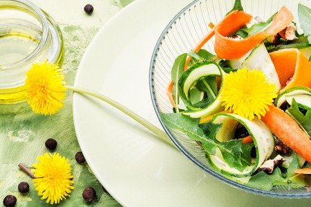 Fresh salad with dandelions flowers,cucumber, arugula and carrot.Diet menu Stock Photo