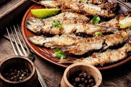 Crispy deep fried small fish on plate