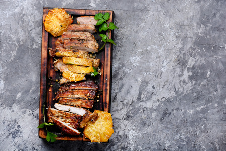 Sliced grilled roast meat with pineapple on wooden cutting board.Top view
