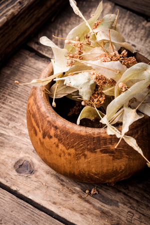 Dried linden flowers on old wooden background.Natural herbs medicine 免版税图像