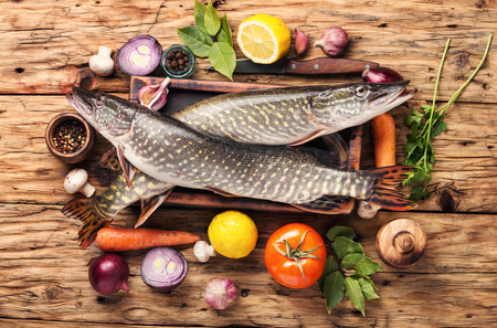 Two raw pike with spices on an old wooden background.Raw fish with spices for cooking.
