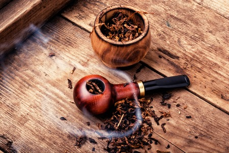Tobacco pipe or smoking pipe on a wooden table