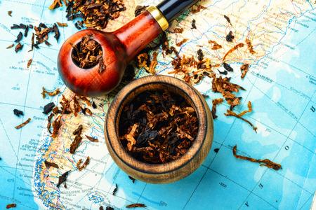 Smoking pipe on the atlas of the world
