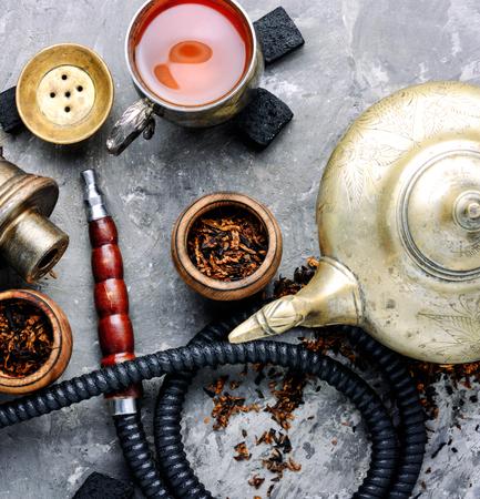 East smoking hookah. Arabian shisha with tea. Hookah and tea.