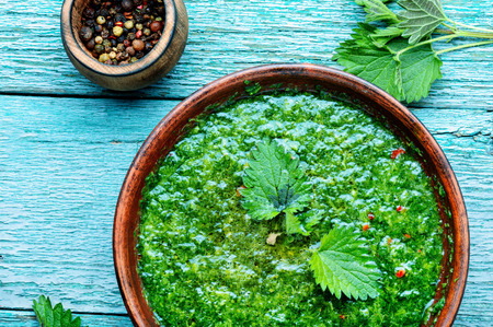Nettle cream soup on wooden background.Soup with fresh nettles