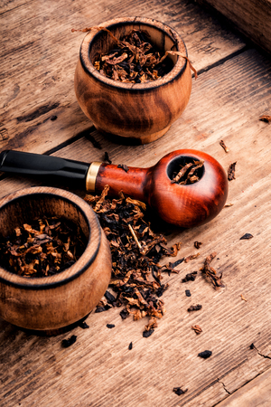 Smoking pipe with tobacco leaves on wooden background
