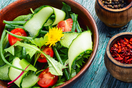 Fresh salad with mixed greens on wooden