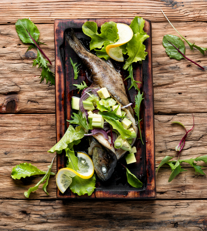 Baked trout with avocado on a wooden kitchen board.Baked fish with lettuce and avacado