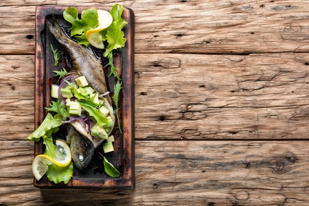 Baked trout with avocado on a wooden kitchen board.
