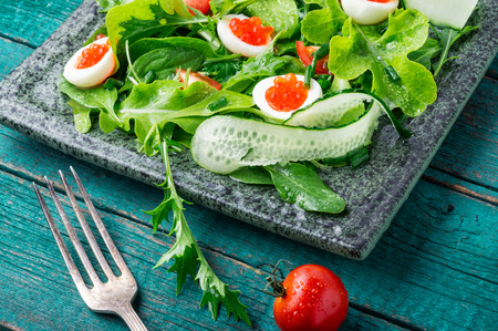 Spring vegetable salad with greens, cucumber, egg and red caviar