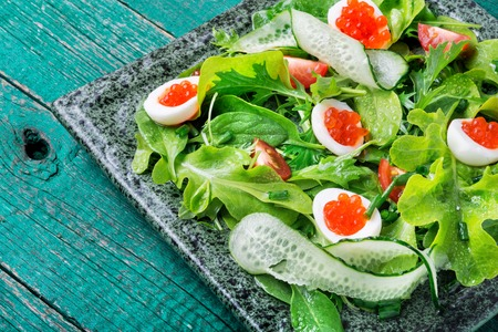 Spring vegetable salad with greens, cucumber, egg and red caviar.Fresh salad with mixed greens