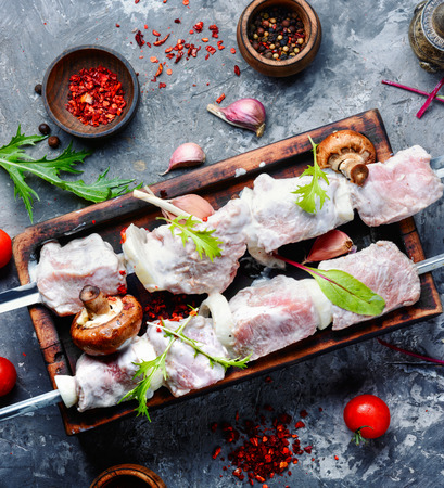Marinated meat with onions and herbs on a cutting board.
