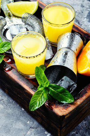 Refreshing cold alcoholic summer citrus cocktail with orange, and ice
