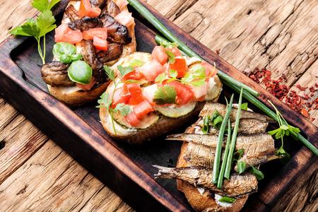 Variety of small sandwiches.Bruschetta on wooden cutting board.Bruschetta is traditional Italian common folk dish.