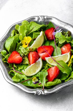 Salad with greens, strawberries and lime.Summer food.Summer dish