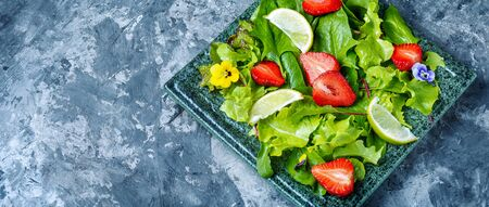 Summer salad with greens, strawberries and lime.Summer food