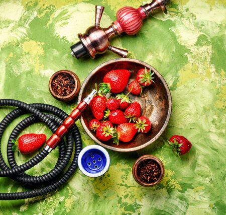 East smoking shisha with tobacco with strawberry flavor.