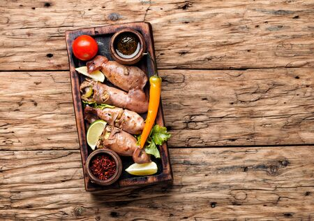 Grilled squid stuffed with vegetables.Seafood on wooden table.Baked squid Archivio Fotografico