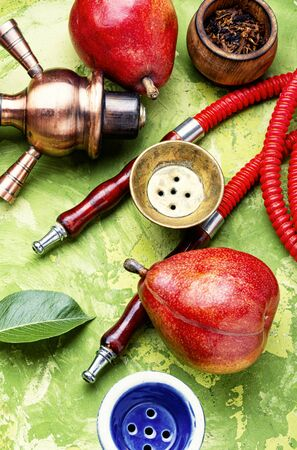 Details of the eastern kalian.Hookah with pear flavor.Smoking pear tobacco Stock Photo - 126411842