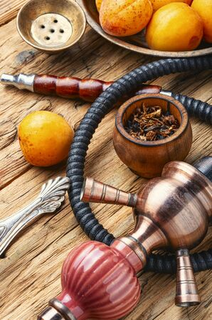 Hookah mouthpiece.Fruit shisha aroma.Tabak with apricot flavor.Kalian smoking with apricot Stock Photo - 126845692