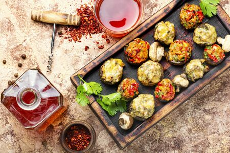Baked mushrooms stuffed with cheese on cutting board.Italian food.Party snack Stock fotó