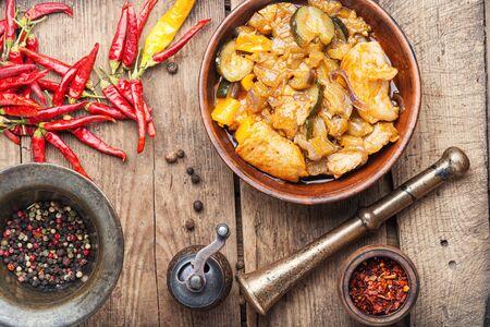 Fleisch mit Auberginen und Pfeffer. Schweinefleisch gekocht mit Gemüse und scharfen Gewürzen. Fleischeintopf mit Gemüse auf rustikalem Holztisch Standard-Bild