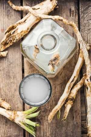 Alcohol tincture from fresh horseradish root.Raw horseradish roots on wooden background Фото со стока