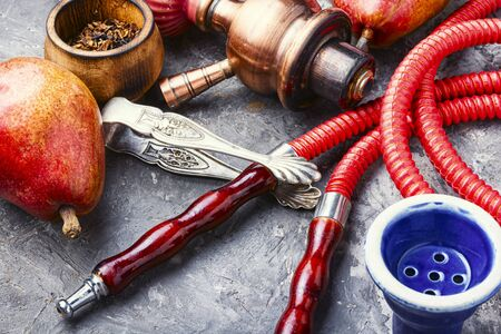 Smoking hookah.Details of Turkish kalian.Shisha with a fruity aroma of tobacco. Фото со стока