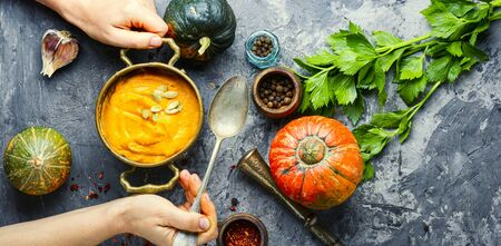 Vegetarian autumn pumpkin cream soup.Bowl of warm pumpkin soup in hands