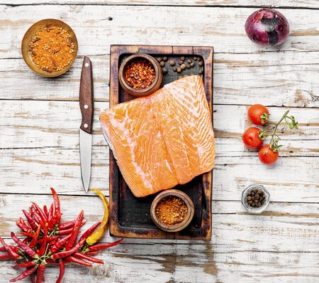Raw salmon fillet with rosemary on wooden cutting board
