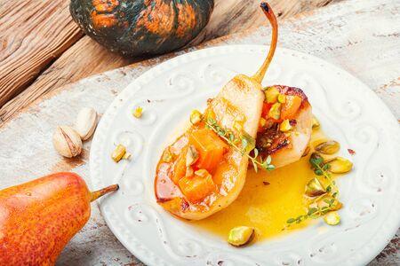 Gevulde perenpompoen en pistache. Herfstvoedsel. Gebakken peren met siroop op plaat Stockfoto