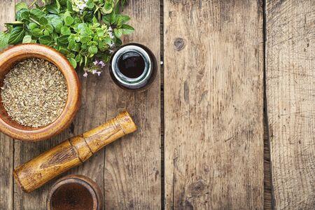 Dried oregano seasoning in a wooden mortar.Herbal medicine Stockfoto