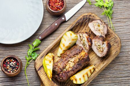 Meatloaf with pears and almonds.Beef meatloaf on wooden table