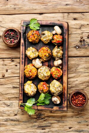 Baked mushrooms stuffed with cheese on cutting board.Italian food.Party snack 写真素材
