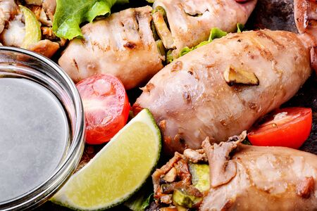 Grilled squid stuffed with vegetables.Seafood on plate.Closeup Stock Photo