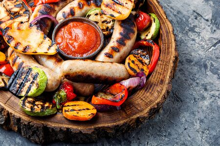 Grilled sausages and vegetables with sauce ketchup on wooden tray.Bbq food