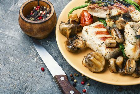 Appetizing grilled steak with mushrooms and herbs on a plate