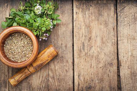 Dried oregano seasoning in a wooden mortar.Herbal medicine Zdjęcie Seryjne