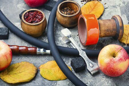 Preparation of a smoking hookah.Oriental hookah with a fruit aroma.Hookah on an apple.