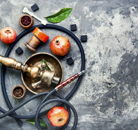 East smoking hookah.Hookah with tobacco with pomegranate taste.Flat lay with copy space Stok Fotoğraf - 134448075