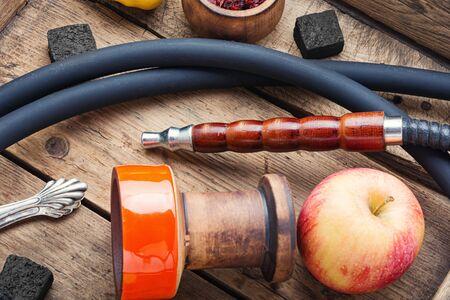 Preparation of a smoking hookah.Oriental hookah with a fruit aroma.Hookah on an apple. Stok Fotoğraf - 134448085