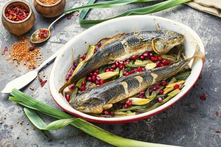 Pelengas fish baked with vegetables and pomegranate.Tasty baked whole fish.Healthy food Stok Fotoğraf